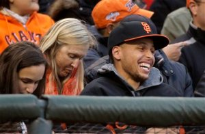 Golden State Warriors guard Stephen Curry laughs while being introduced during the second inning of baseball game between the San Francisco Giants and the Atlanta Braves on Friday, May 29, 2015, in San Francisco. (AP Photo/Eric Risberg)
