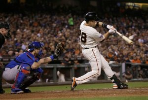 San Francisco Giants' Buster Posey, right, hits a single in front of Chicago Cubs catcher Miguel Montero during the sixth inning of a baseball game in San Francisco, Tuesday, Aug. 25, 2015. (AP Photo/Jeff Chiu)